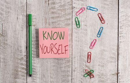 Word writing text Know Yourself. Business photo showcasing Find You Understanding Strength and Weaknesses Identity Pastel colour note paper placed next to stationary above the wooden table