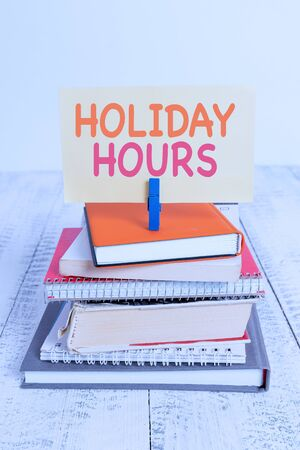 Conceptual hand writing showing Holiday Hours. Concept meaning employee receives twice their normal pay for all hours pile stacked books notebook pin color reminder white wooden