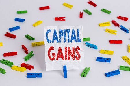 Text sign showing Capital Gains. Business photo showcasing Bonds Shares Stocks Profit Income Tax Investment Funds Colored clothespin papers empty reminder white floor background office