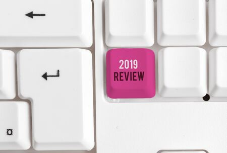 Conceptual hand writing showing 2019 Review. Concept meaning New trends and prospects in tourism or services for 2019 White pc keyboard with note paper above the white background Stock Photo