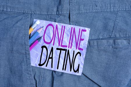 Conceptual hand writing showing Online Dating. Concept meaning Searching Matching Relationships eDating Video Chatting Writing equipment and purple note paper inside pocket of trousers Фото со стока