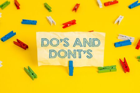 Writing note showing Do S And Dont S. Business concept for Rules or customs concerning some activity or actions Colored clothespin papers empty reminder yellow floor background office