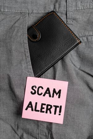 Conceptual hand writing showing Scam Alert. Concept meaning fraudulently obtain money from victim by persuading him Small wallet inside trouser front pocket near notation paper Stock Photo