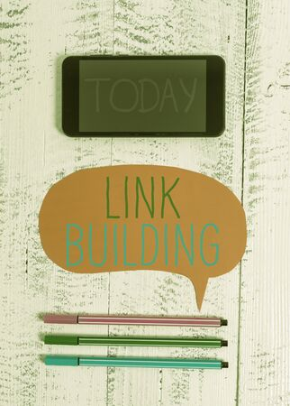 Writing note showing Link Building. Business concept for SEO Term Exchange Links Acquire Hyperlinks Indexed Smartphone cell pens blank colored speech bubble wooden background Stock Photo