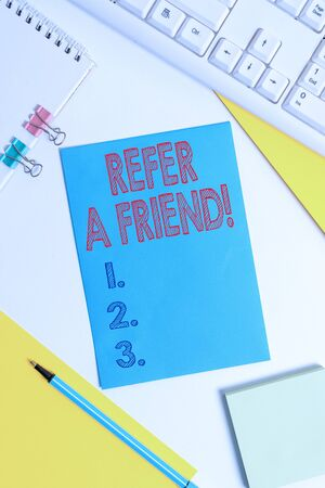 Conceptual hand writing showing Refer A Friend. Concept meaning direct someone to another or send him something like gift Colored paper binder clip sheets white desk empty space Stock Photo