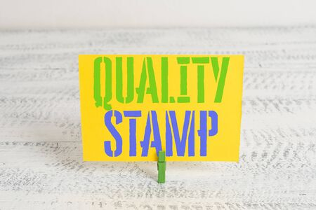 Text sign showing Quality Stamp. Business photo showcasing Seal of Approval Good Impression Qualified Passed Inspection Green clothespin white wood background colored paper reminder office supply Imagens