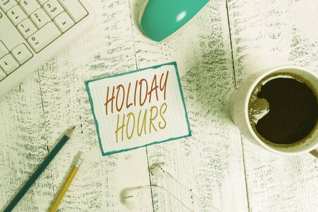 Writing note showing Holiday Hours. Business concept for employee receives twice their normal pay for all hours Technological devices colored reminder paper office supplies