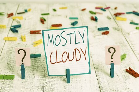 Conceptual hand writing showing Mostly Cloudy. Concept meaning Shadowy Vaporous Foggy Fluffy Nebulous Clouds Skyscape Crumbling sheet with paper clips placed on the wooden table