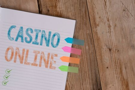 Handwriting text writing Casino Online. Conceptual photo Computer Poker Game Gamble Royal Bet Lotto High Stakes Striped note book four colored arrow banners reminder wooden background