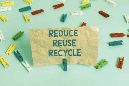Text sign showing Reduce Reuse Recycle. Business photo text environmentallyresponsible consumer behavior Colored clothespin papers empty reminder blue floor background office pin