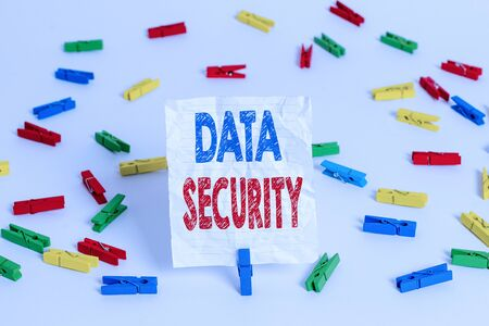 Text sign showing Data Security. Business photo showcasing Confidentiality Disk Encryption Backups Password Shielding Colored clothespin papers empty reminder white floor background office Banco de Imagens