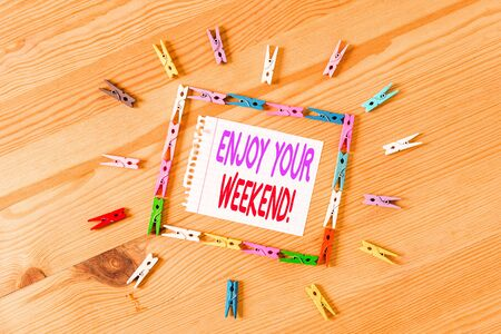 Handwriting text writing Enjoy Your Weekend. Conceptual photo wishing someone that something nice will happen at holiday Colored clothespin papers empty reminder wooden floor background office