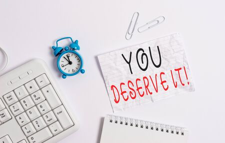 Writing note showing You Deserve It. Business concept for should have it because of their qualities or actions Blank paper with copy space on the table with clock and pc keyboard