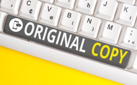 Conceptual hand writing showing Original Copy. Concept meaning Main Script Unprinted Branded Patented Master List White pc keyboard with note paper above the white background Stock Photo