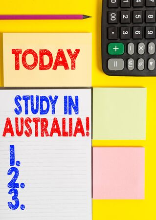 Writing note showing Study In Australia. Business concept for going into foreign country order complete your studies Colored empty papers with copy space on the yellow background table