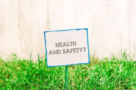 Handwriting text Health And Safety Question. Conceptual photo regulations and procedures to prevent accident or injury Plain empty paper attached to a stick and placed in the green grassy land