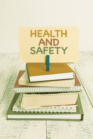 Conceptual hand writing showing Health And Safety. Concept meaning procedures intended to prevent accident in workplace pile stacked books notebook pin color reminder white wooden