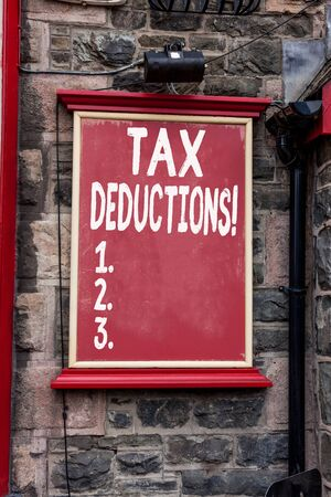 Conceptual hand writing showing Tax Deductions. Concept meaning reduction income that is able to be taxed of expenses Blank board copy space for commercial advertising on wall Stock Photo