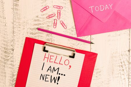 Conceptual hand writing showing Hello I Am New. Concept meaning used greeting or begin telephone conversation Colored clipboard paper sheet pencil clips wooden background