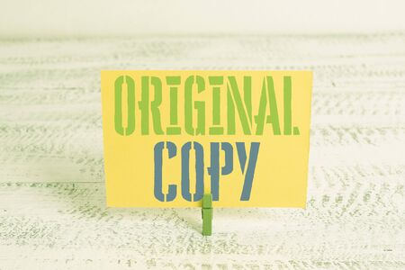 Text sign showing Original Copy. Business photo showcasing Main Script Unprinted Branded Patented Master List Green clothespin white wood background colored paper reminder office supply Stock Photo