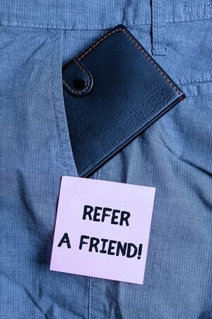 Conceptual hand writing showing Refer A Friend. Concept meaning direct someone to another or send him something like gift Small wallet inside trouser front pocket near notation paper