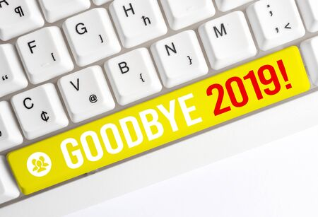 Word writing text Goodbye 2019. Business photo showcasing express good wishes when parting or at the end of last year White pc keyboard with empty note paper above white background key copy space