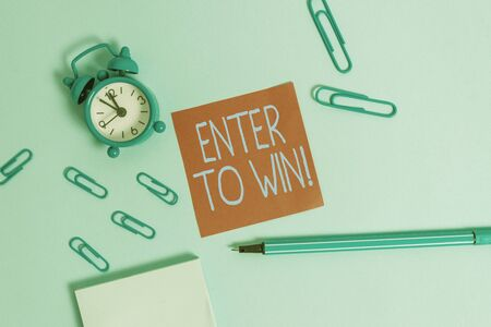 Conceptual hand writing showing Enter To Win. Concept meaning exchanging something value for prize chance winning prize Alarm clock notepad sticky note marker colored background