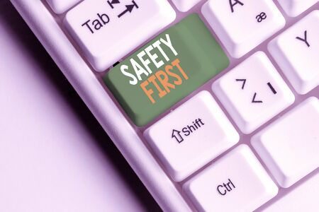 Handwriting text Safety First. Conceptual photo used to say that the most important thing is to be safe White pc keyboard with empty note paper above white background key copy space 스톡 콘텐츠