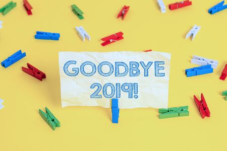 Writing note showing Goodbye 2019. Business concept for express good wishes when parting or at the end of last year Colored clothespin papers empty reminder yellow floor background office Imagens