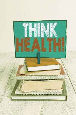 Writing note showing Think Health. Business concept for state of complete physical mental and social well being pile stacked books notebook pin color reminder white wooden Banco de Imagens