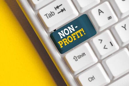 Conceptual hand writing showing NonProfit. Concept meaning not making or conducted primarily to make profit organization White pc keyboard with note paper above the white background