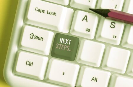 Writing note showing Next Steps. Business concept for something you do after you have finished doing first one White pc keyboard with note paper above the white background