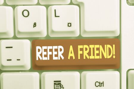 Writing note showing Refer A Friend. Business concept for direct someone to another or send him something like gift White pc keyboard with note paper above the white background Stock Photo