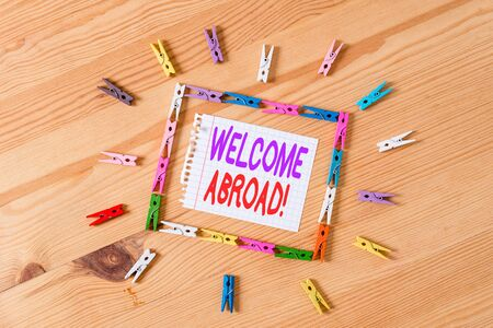 Handwriting text writing Welcome Abroad. Conceptual photo something that you say when someone gets on ship Colored clothespin papers empty reminder wooden floor background office Stock fotó