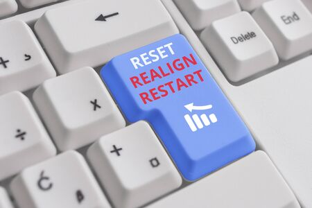 Conceptual hand writing showing Reset Realign Restart. Concept meaning Life audit will help you put things in perspectives White pc keyboard with note paper above the white background Stock Photo