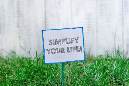 Handwriting text Simplify Your Life. Conceptual photo focused on important and let someone else worry about less ones Plain empty paper attached to a stick and placed in the green grassy land