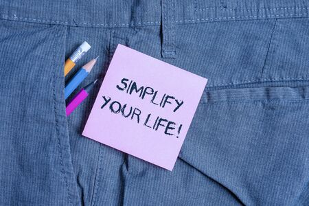 Conceptual hand writing showing Simplify Your Life. Concept meaning focused on important and let someone else worry about less ones Writing equipment and pink note paper inside pocket of trousers
