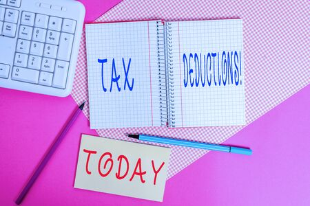 Text sign showing Tax Deductions. Business photo text reduction income that is able to be taxed of expenses Writing equipments and computer stuffs placed above colored plain table
