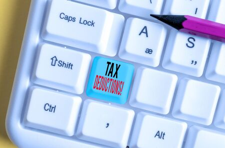 Conceptual hand writing showing Tax Deductions. Concept meaning reduction income that is able to be taxed of expenses White pc keyboard with note paper above the white background Stock Photo