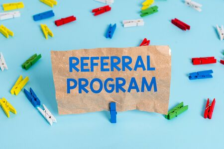 Text sign showing Referral Program. Business photo text employees are rewarded for introducing suitable recruits Colored clothespin papers empty reminder blue floor background office pin