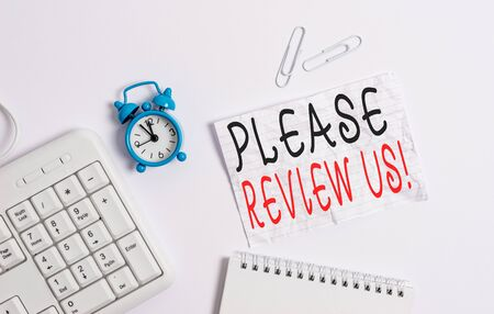 Writing note showing Please Review Us. Business concept for situation or system is formal examination by showing authority Blank paper with copy space on the table with clock and pc keyboard