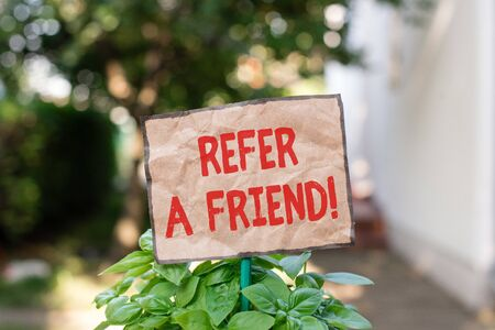 Writing note showing Refer A Friend. Business concept for direct someone to another or send him something like gift Plain paper attached to stick and placed in the grassy land