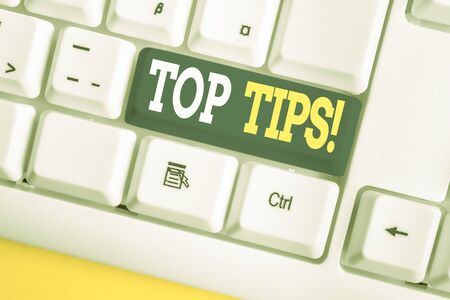 Word writing text Top Tips. Business photo showcasing small but particularly useful piece of practical advice White pc keyboard with empty note paper above white background key copy space Stock fotó