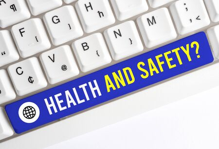 Writing note showing Health And Safety Question. Business concept for regulations and procedures to prevent accident or injury White pc keyboard with note paper above the white background 写真素材 - 129850532
