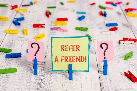 Handwriting text Refer A Friend. Conceptual photo direct someone to another or send him something like gift Scribbled and crumbling sheet with paper clips placed on the wooden table