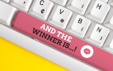 Writing note showing And The Winner Is. Business concept for announcing who got first place at competition or exam White pc keyboard with note paper above the white background