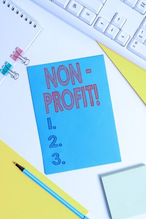Conceptual hand writing showing NonProfit. Concept meaning not making or conducted primarily to make profit organization Colored paper binder clip sheets white desk empty space Stockfoto