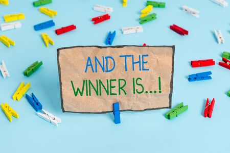 Handwriting text writing And The Winner Is. Conceptual photo announcing who got first place at competition or exam Colored clothespin papers empty reminder blue floor background office pin Фото со стока
