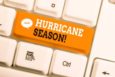 Text sign showing Hurricane Season. Business photo showcasing time when most tropical cyclones are expected to develop White pc keyboard with empty note paper above white background key copy space