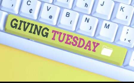 Text sign showing Giving Tuesday. Business photo text international day of charitable giving Hashtag activism White pc keyboard with empty note paper above white background key copy space